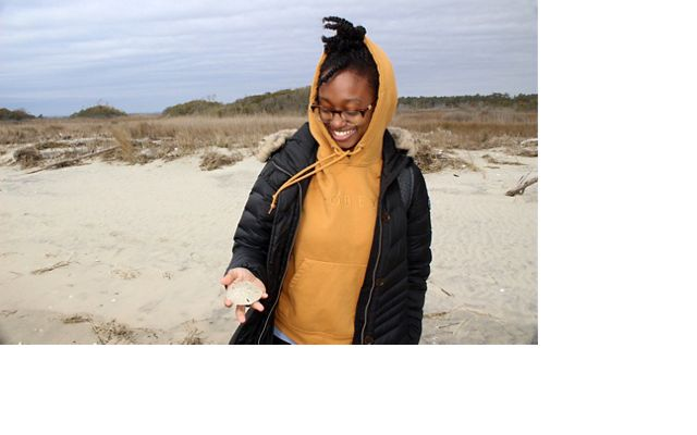 A woman holds a sand dollar in her hand.