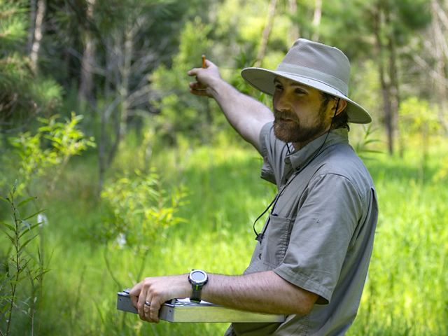 Candid photo of Wetland Restoration Assistant Alex Fisher in the field. A man wearing a wide brimmed hat holds a metal clipboard in one hand and gestures with the other hand, pointing behind him.