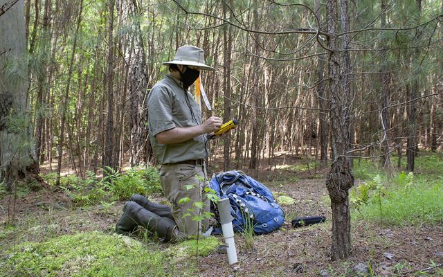 A man sits on his knees recording data into a hand held tablet that it attached to a length of tube in the ground.