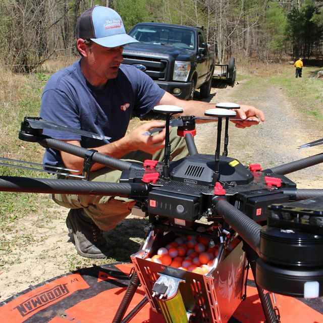 A man crouches on the ground next to a large drone, readying it for deployment on a controlled burn. The drone is sitting on a round orange landing pad.