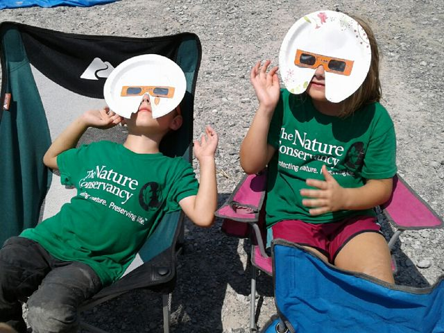Two children wear homemade solar eclipse glasses made from paper plates.