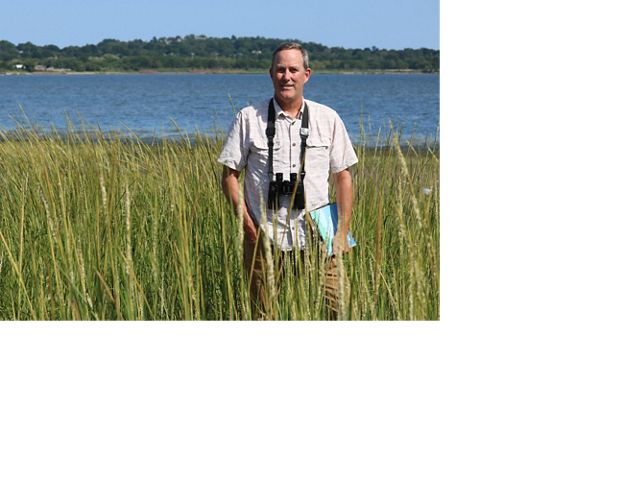 Man standing in marsh with binoculars.