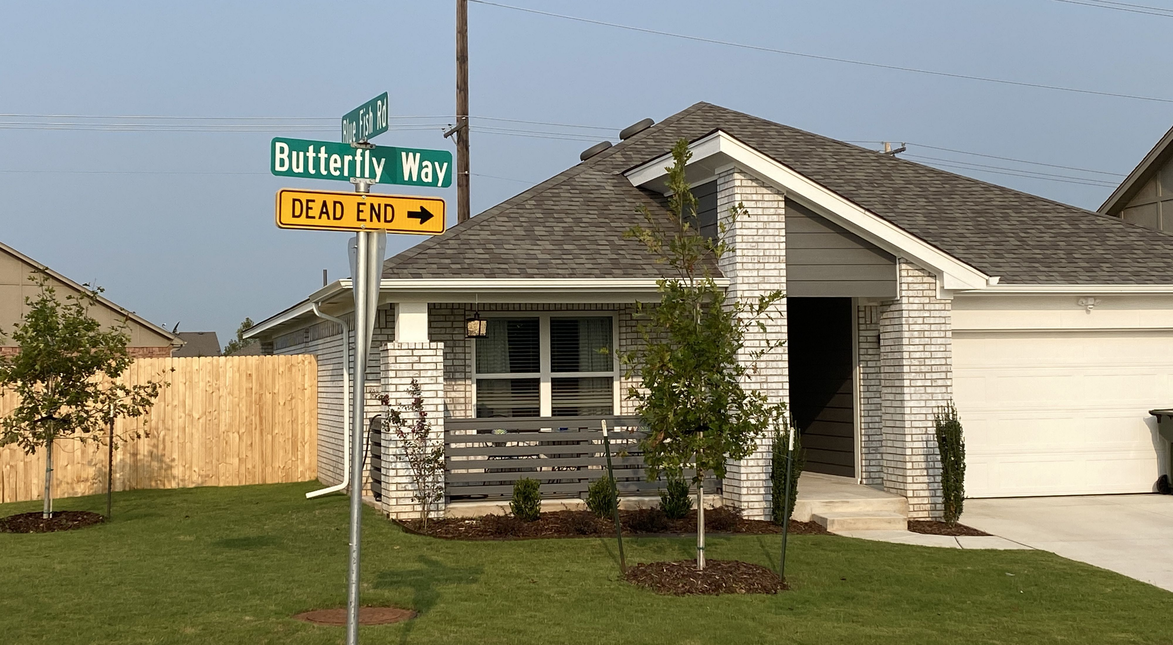 """A street sign named """"Butterfly Way"""" leading towards pollinator gardens in a housing addition."""