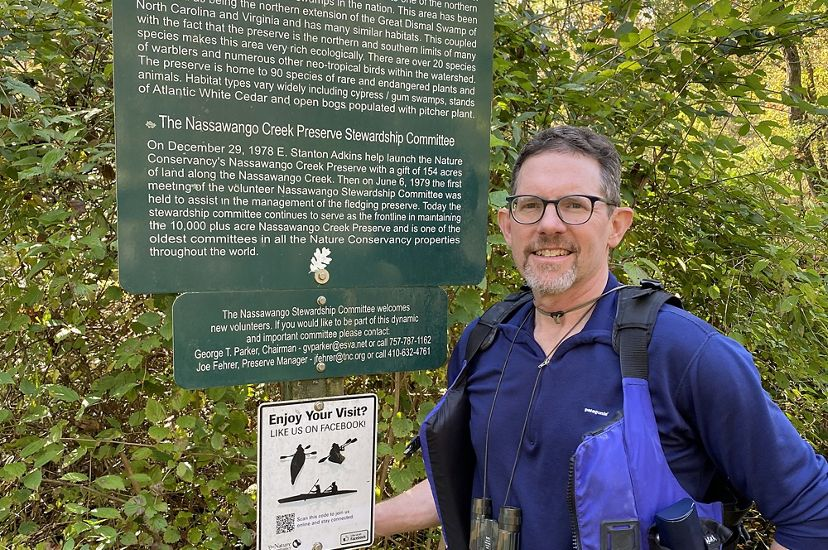 Candid snapshot of MD/DC Deputy Development Director Steve Volkers. A man wearing a blue shirt and blue personal flotation device stands next to a green information sign at Nassawango Creek Preserve.