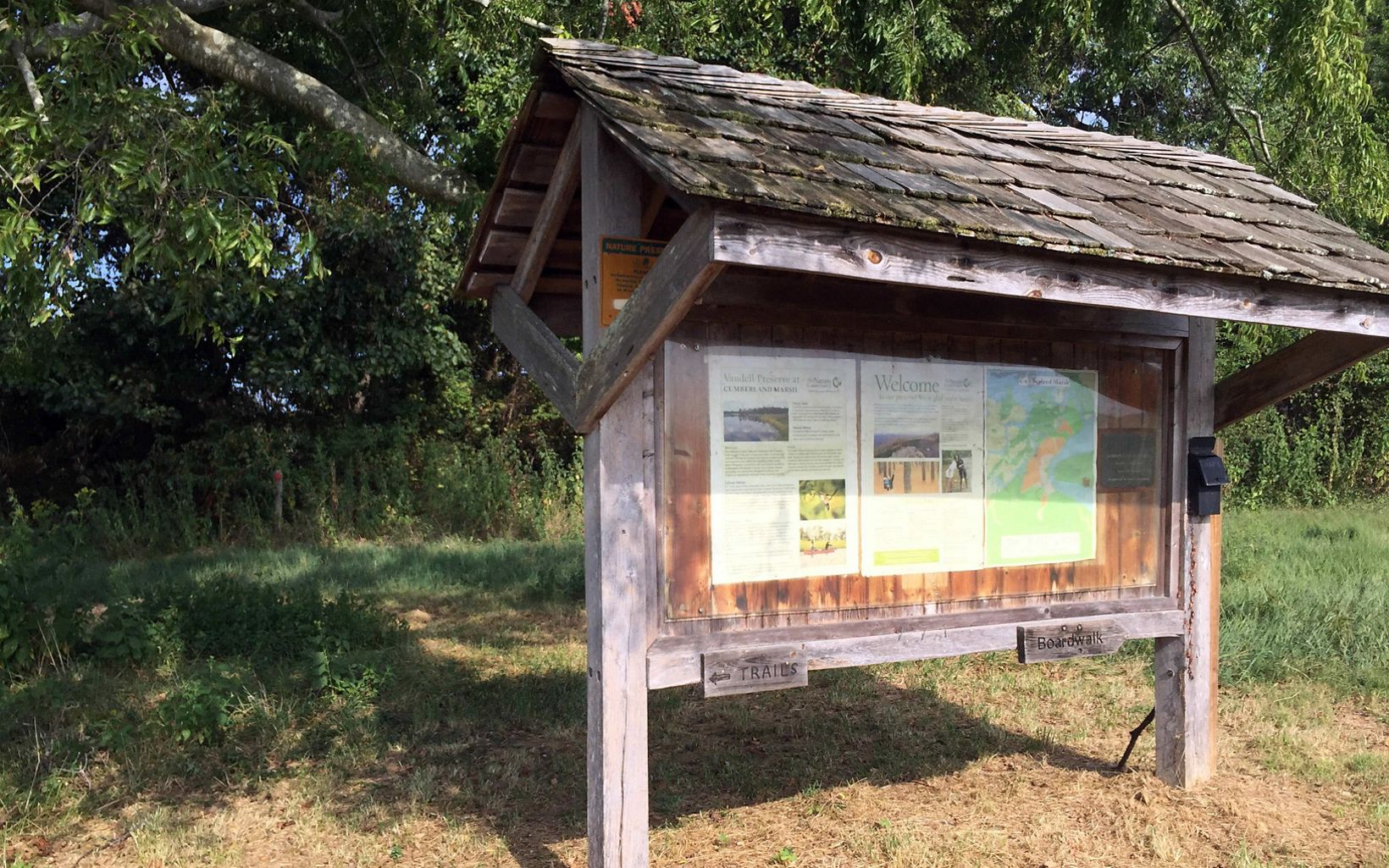 Preserve visitor kiosk. The large wooden message board is protected by an overhanging shingled roof.