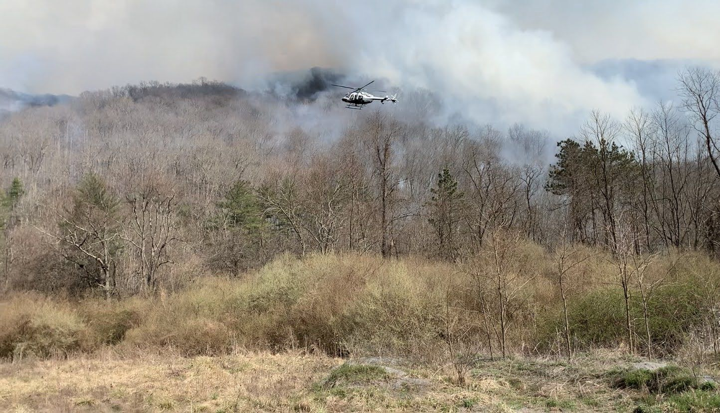 A white helicopter flies over a forest during a controlled burn. White smoke rises from the forest floor. The terrain rises into a ridge top in the background.