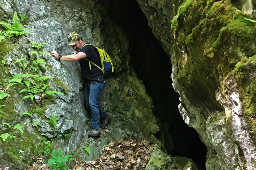 A man balances on a narrow rock ledge as he carefully inches his way out of a mountain cave.
