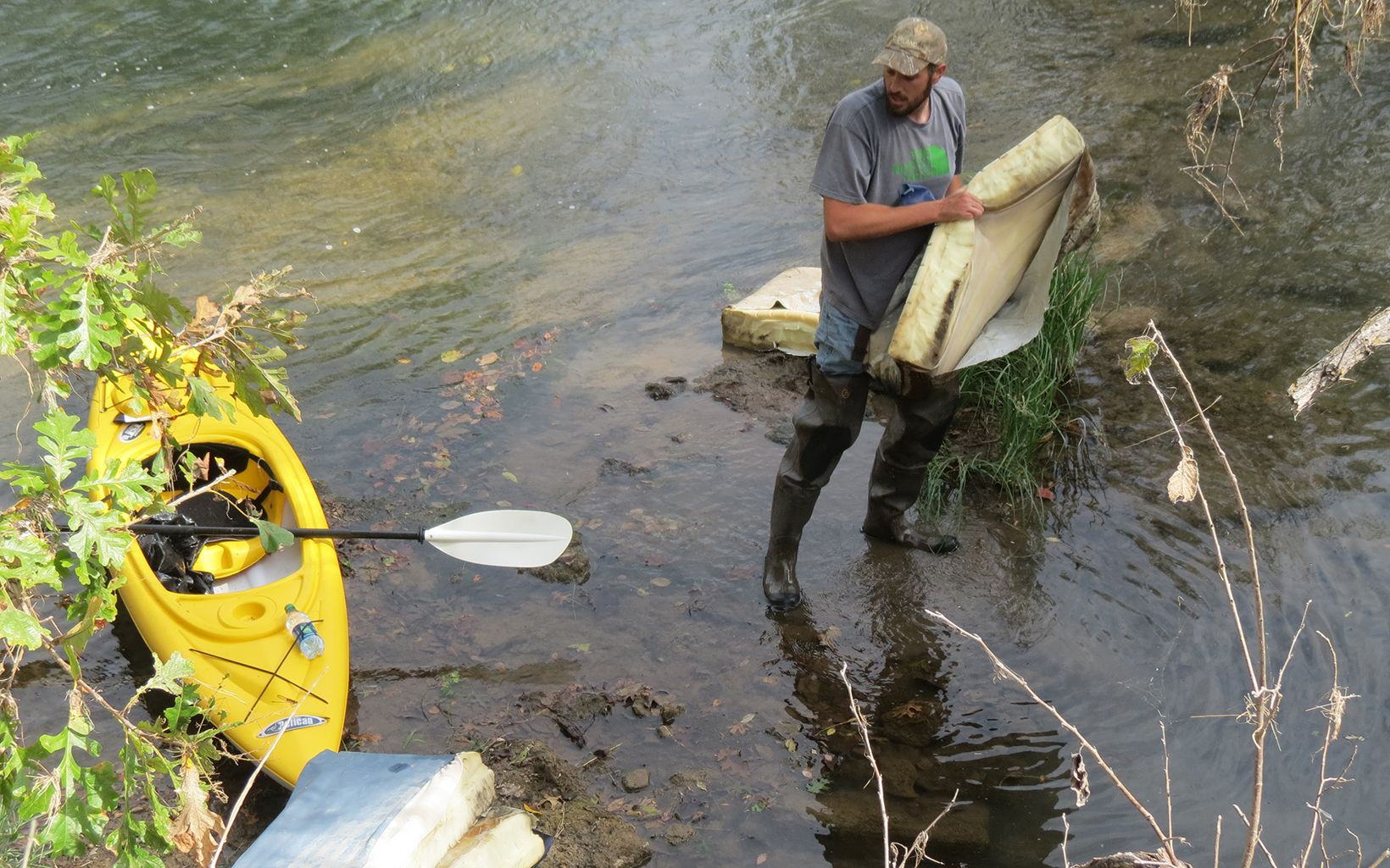 Volunteer cleaning up along Blue River