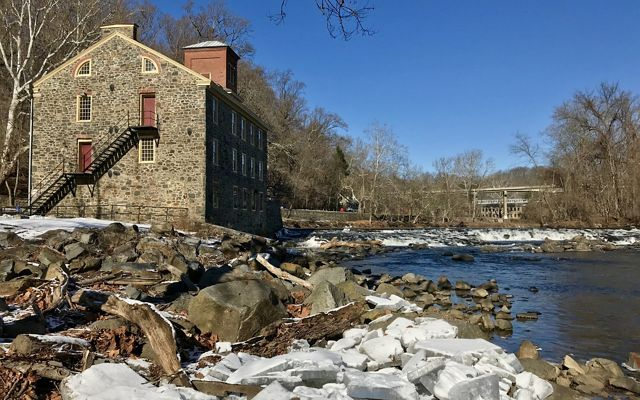 Water rushes over low falls on a narrow creek. Large stones and riprap edge the creek bank in the foreground.