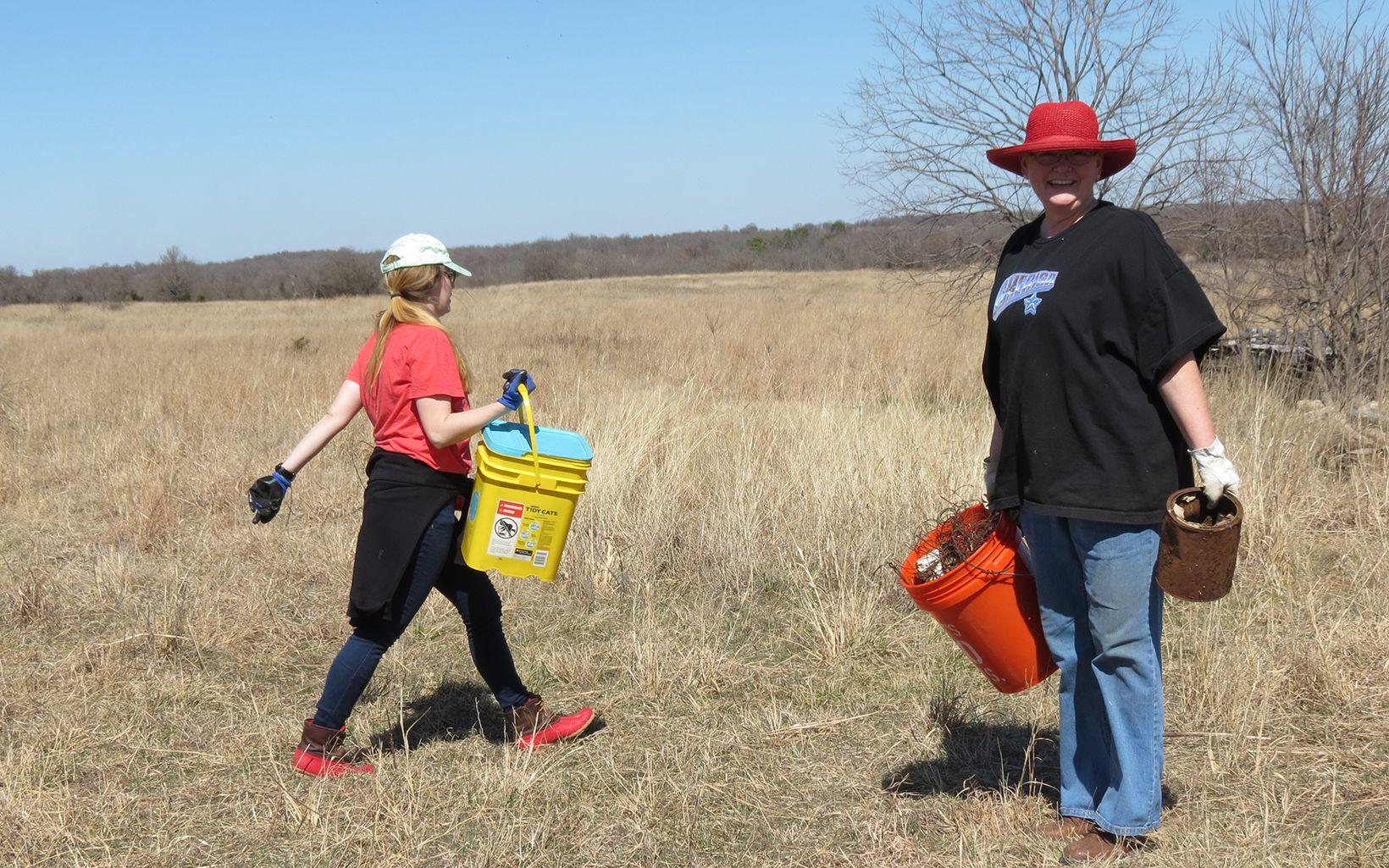 Volunteer picking up trash along Blue River