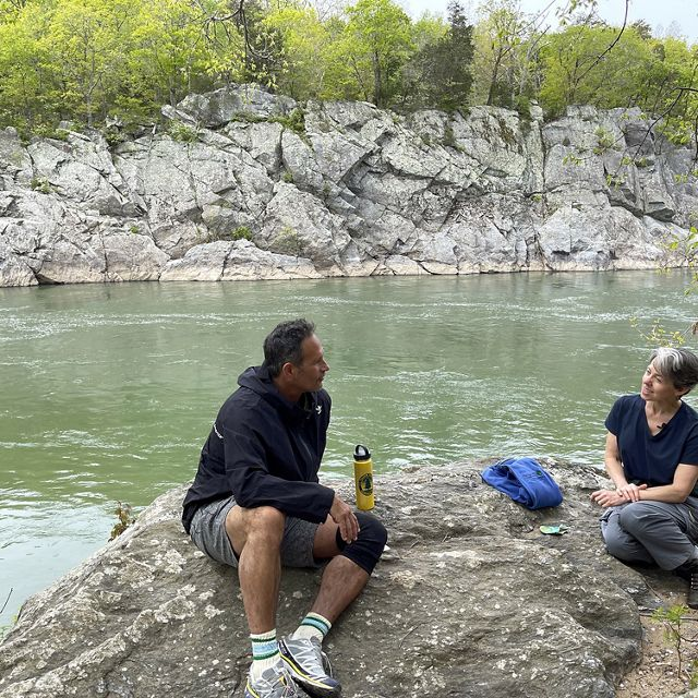 A man and a woman sit on a rock outcropping at the edge of the Potomac River. The water flows between a narrow, rocky gorge. Trees grow on top of the rocks lining the river in the background.