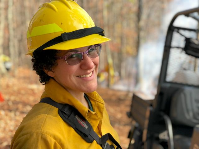 A smiling woman wearing yellow protective fire gear and a yellow hard hat. White smoke rises behind her from a small fire.