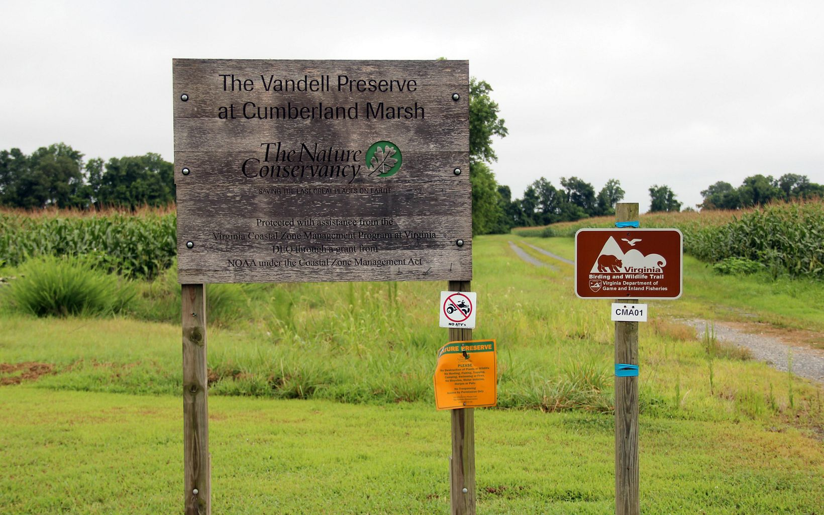 A large wooden sign welcomes visitors to Cumberland Marsh. A dirt lane curves off the right past a field of tall corn.