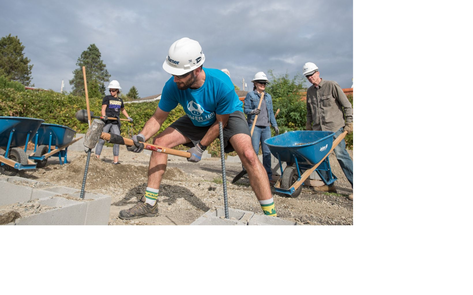 Volunteers and staff build garden plots with cinderblock and fill soil at the Paradise Parking Plots Community Garden.