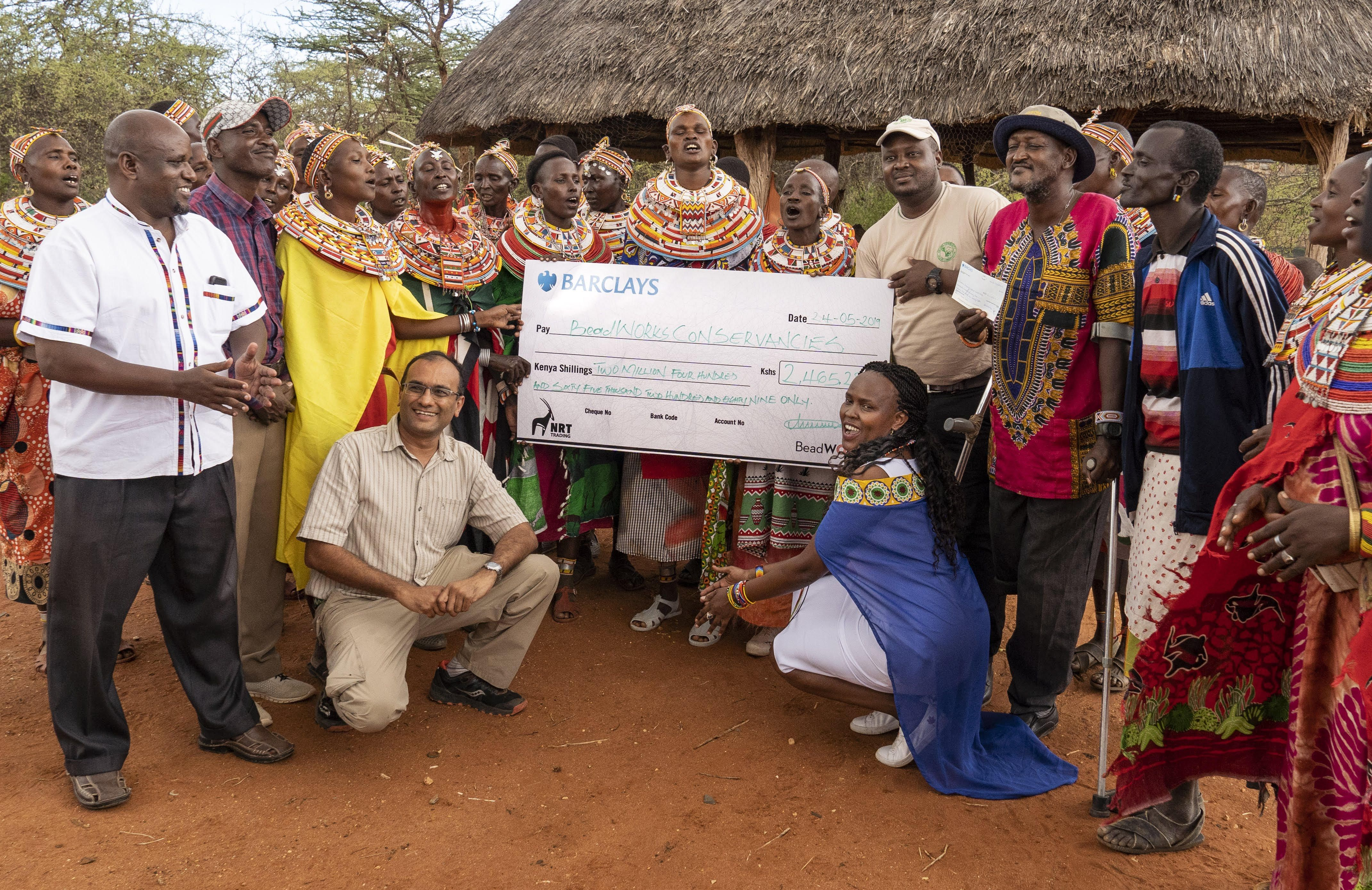 A group of people pose while holding a large check.