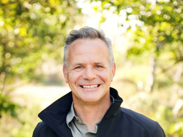 Man smiling at the camera wearing a black jacket with The Nature Conservancy logo on the right lapel.
