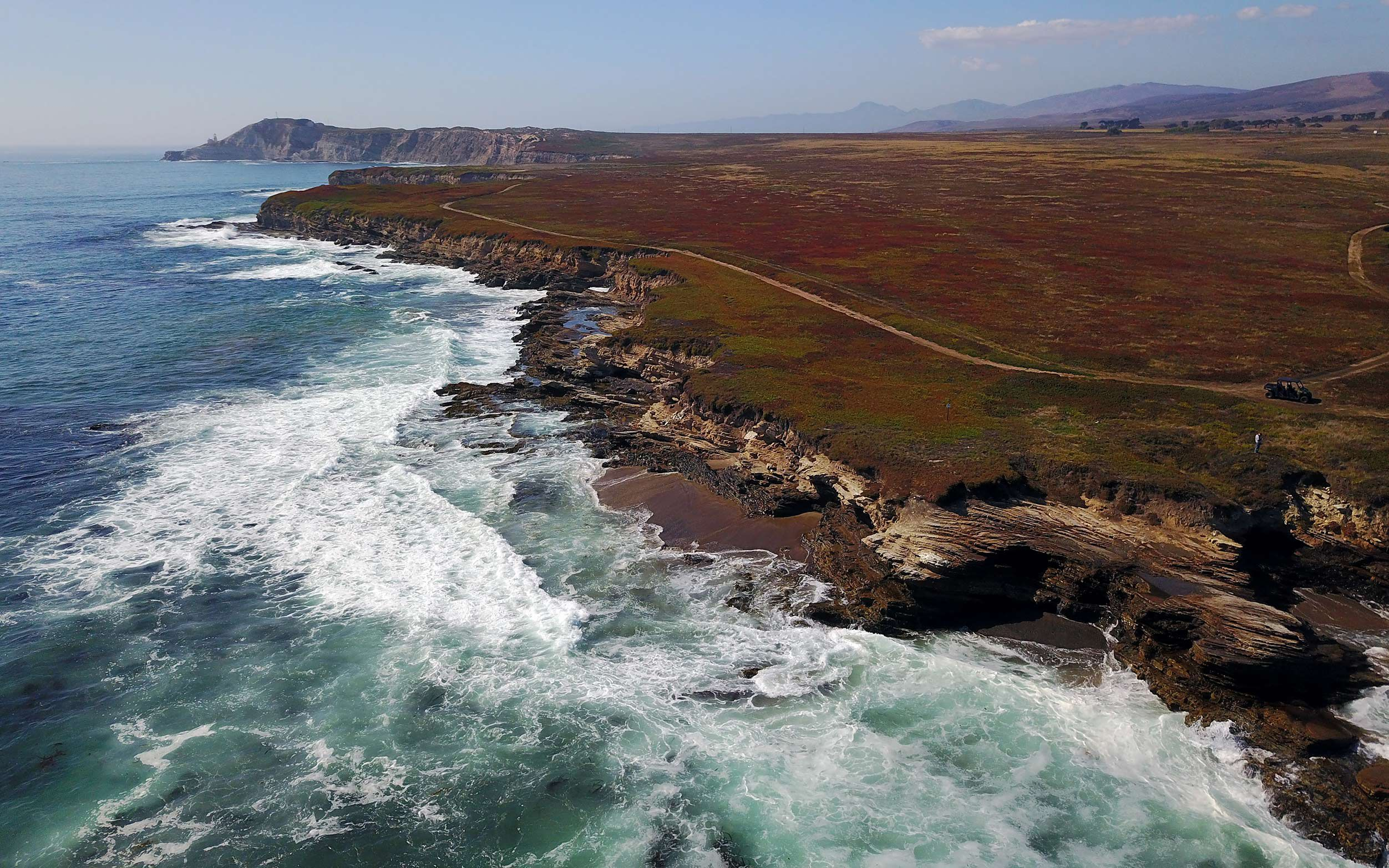 Aerial view of the coastline of Dangermond preserve with turquoise waves breaking on a rocky shore.