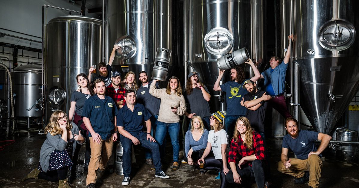 A group of brewery staff members pose near stainless steel barrels.