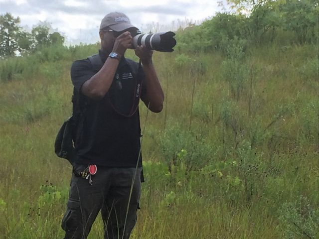 Our fellow Jajuan takes a picture with a large camera while standing in a field of prairie grass.