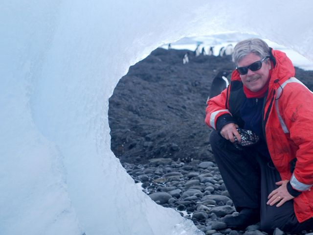 Dr. James McClintock in front of an iceberg.
