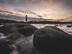 A young girl stands on a large flat boulder laying at the edge of the James River. Other boulders dot the water around her. The sun is rising behind low clouds on the horizon.