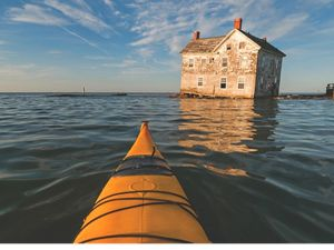 An abandoned farm house sits precariously at the edge of the water as the Chesapeake Bay slowly consumes it. The yellow nose of a kayak is visible in the foreground.
