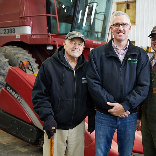 Three men standing in front of a red combine.