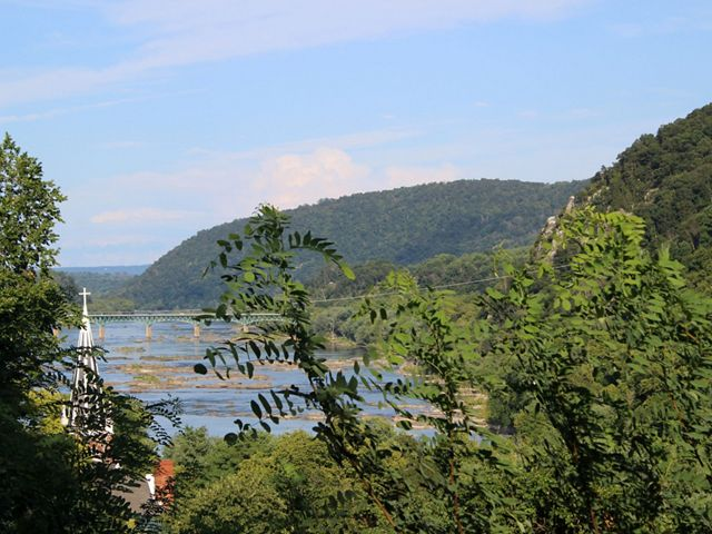 View through tree branches of the Potomac River as it winds between green mountains and the town of Harpers Ferry.