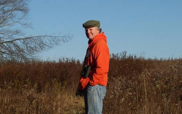 A man in an orange jacket and green cap stops along a grassy trail to pose for a photo.