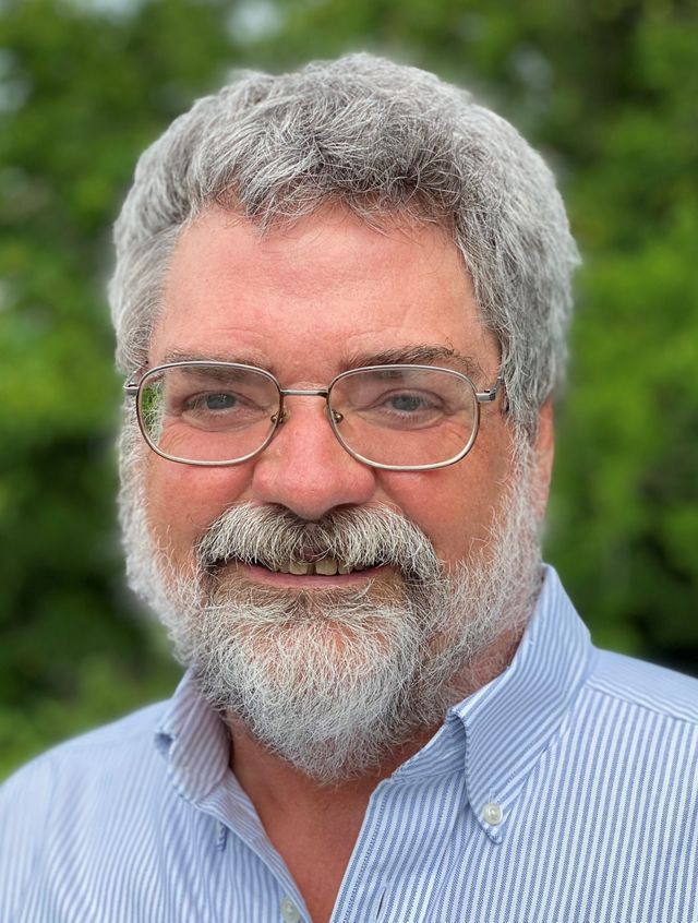 Headshot of Land Protection Manager Jim McGowan. A smiling man with a greying beard poses in front of a tall green bush.