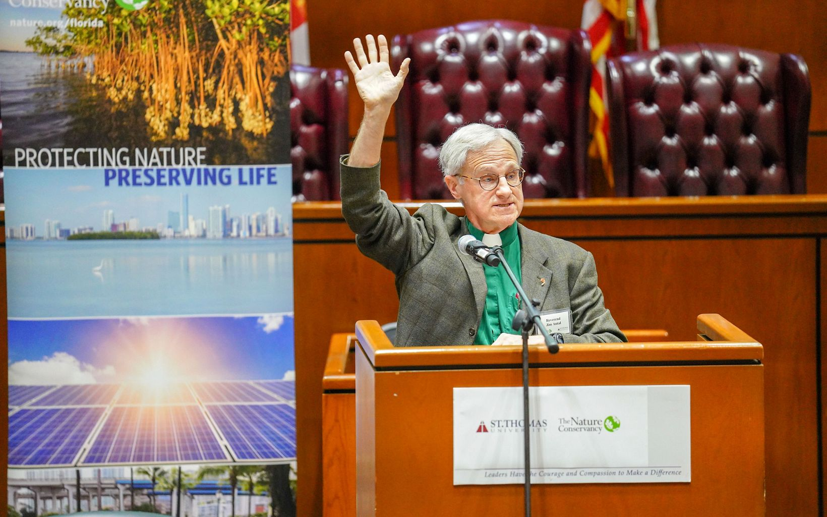 Reverend Dr. Jim Antal standing at a podium speaking with one hand raised in the air.