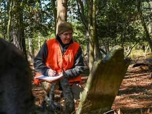 Joe Fehrer records information from historic graves that could be lost due to sea level rise at Robinson Neck Preserve.