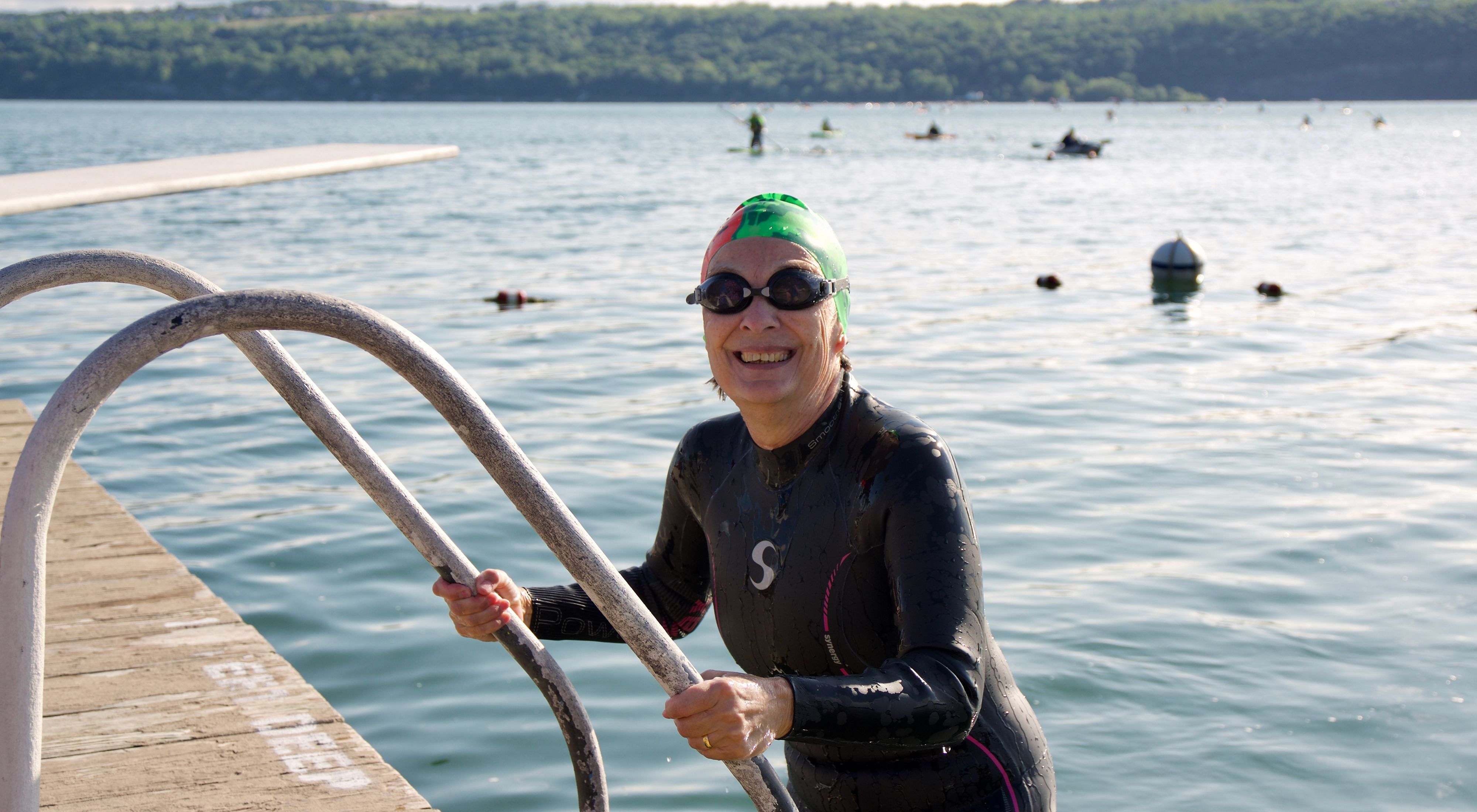 A swimmer in a long sleeved black wetsuit and green swim cap with goggles on emerging from a lake on a ladder and dock at the lefthand side of the frame.