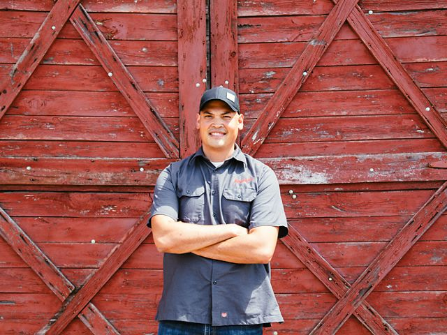 John Hensley in Leinenkugel's baseball cap and work shirt stands with arms crossed, in front of red, wooden barn doors.