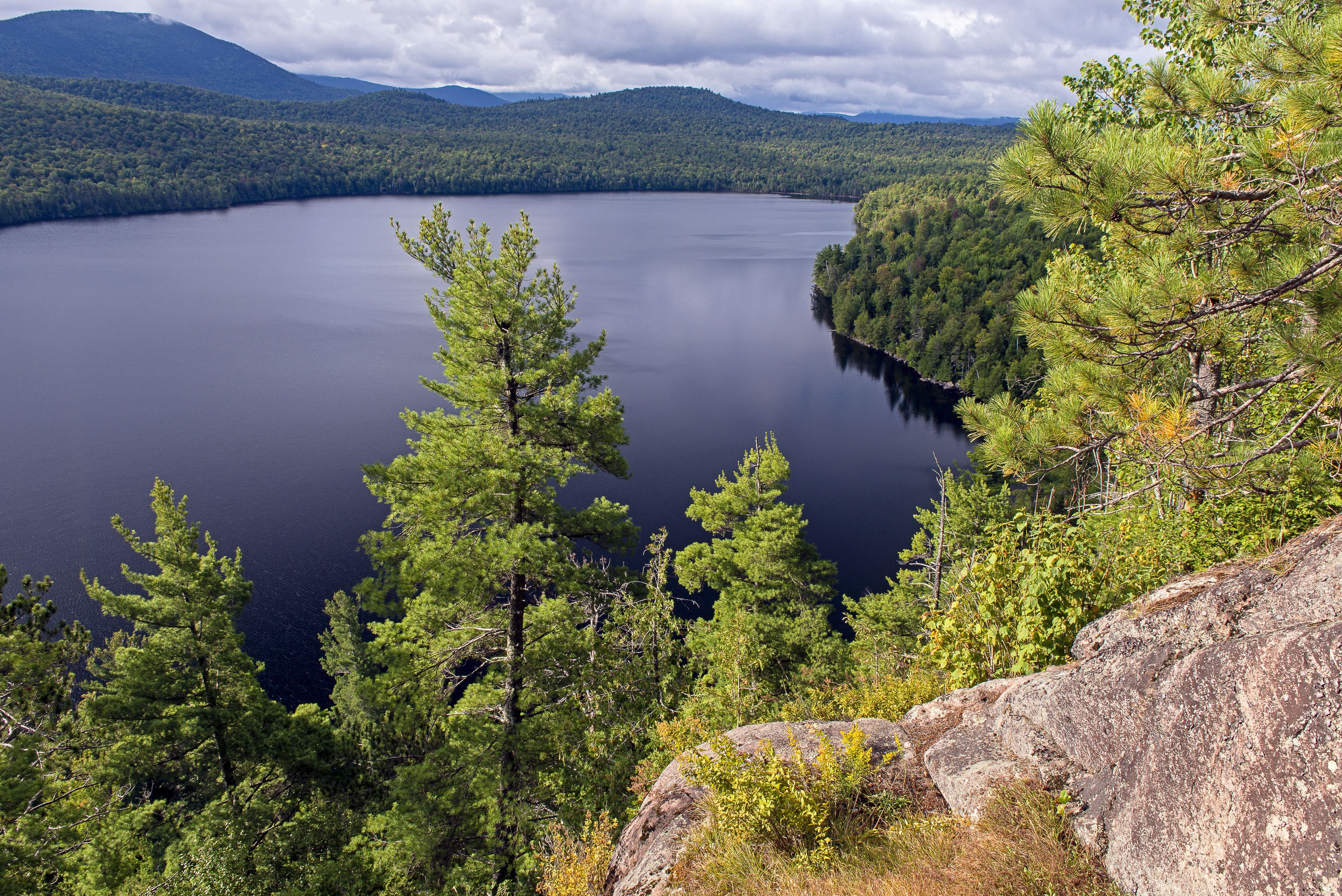 A view from atop a gray boulder on the righthand side of the image looking out onto a blue lake with green trees lining the shore.