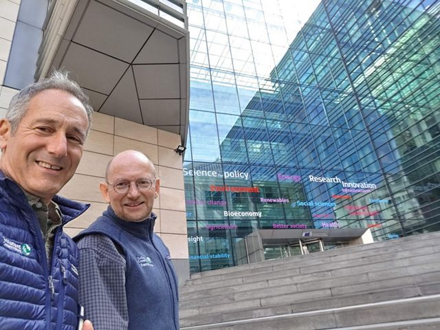 "Josh Royte and Andras Krolopp in front of a glass-walled building with words like ""science"", ""policy"", ""innovation"" on it."