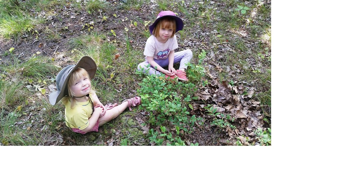 Two young girls in hats sit on the forest floor.
