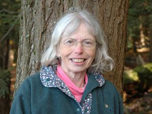A woman with glasses and gray hair in front of a tree.
