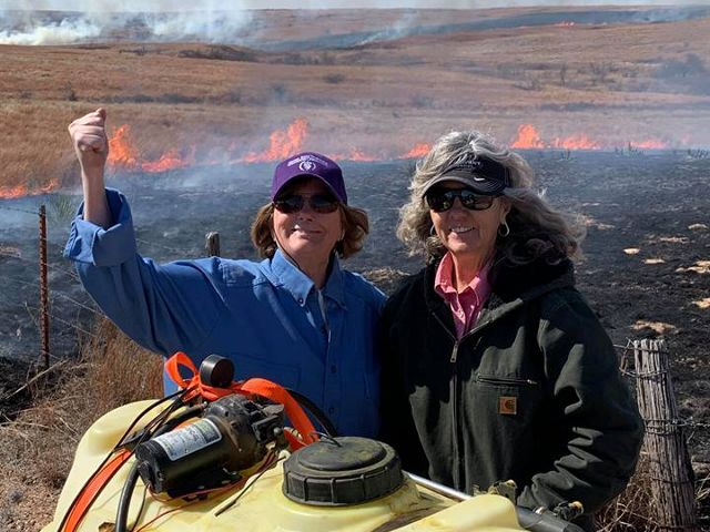 Two female ranchers conducting a prescribed burn.