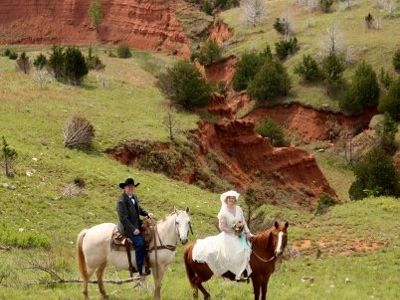 Man and women taking wedding photos on horseback overlooking a ridge crevice shaped like a heart.