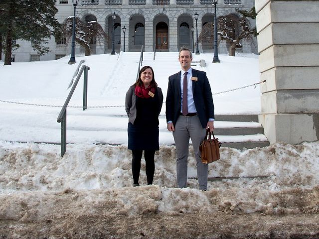 Kaitlyn Bernard and Rob Wood stand in front of the Maine State House on a snowy day.