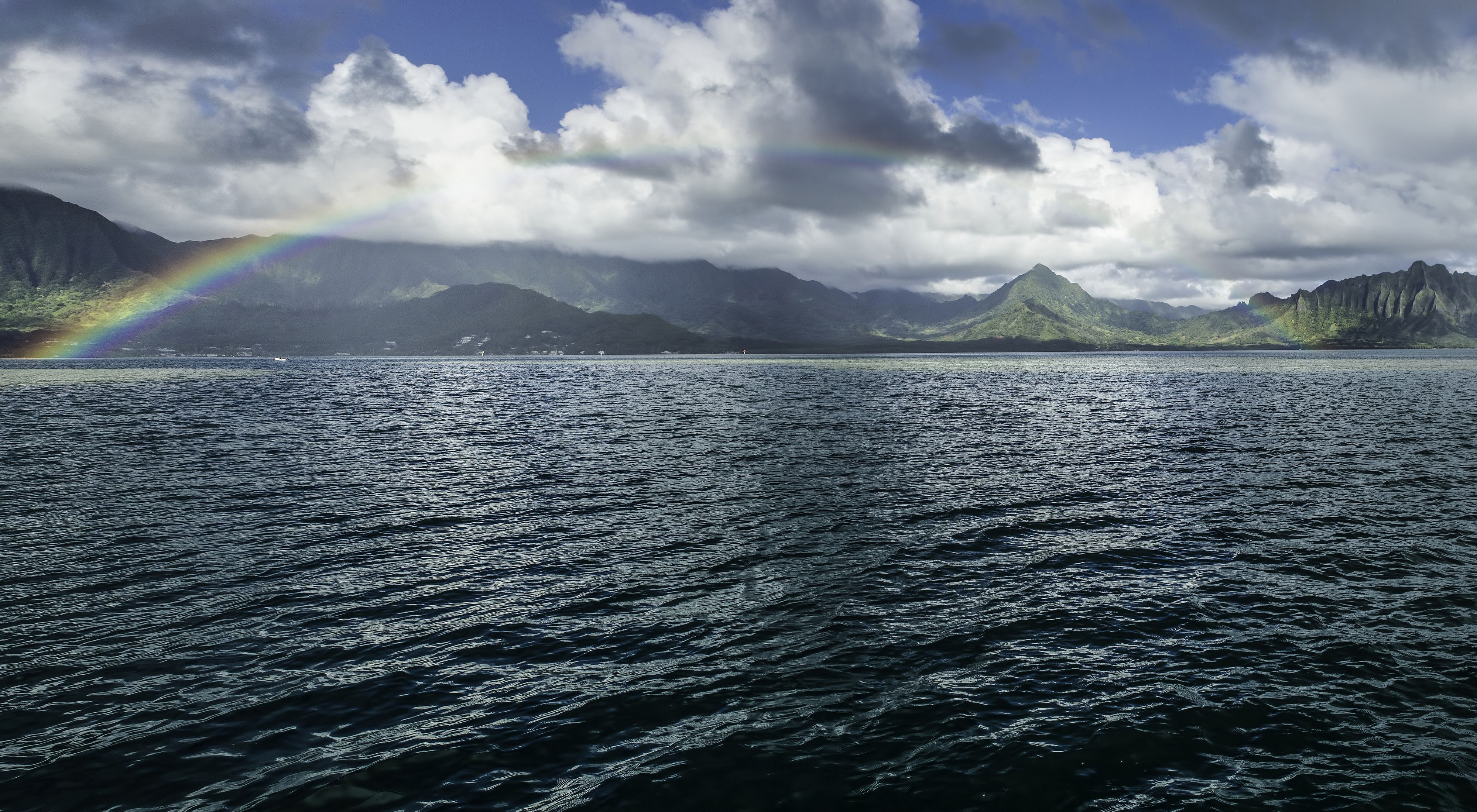 a rainbow arching over mountains and sea