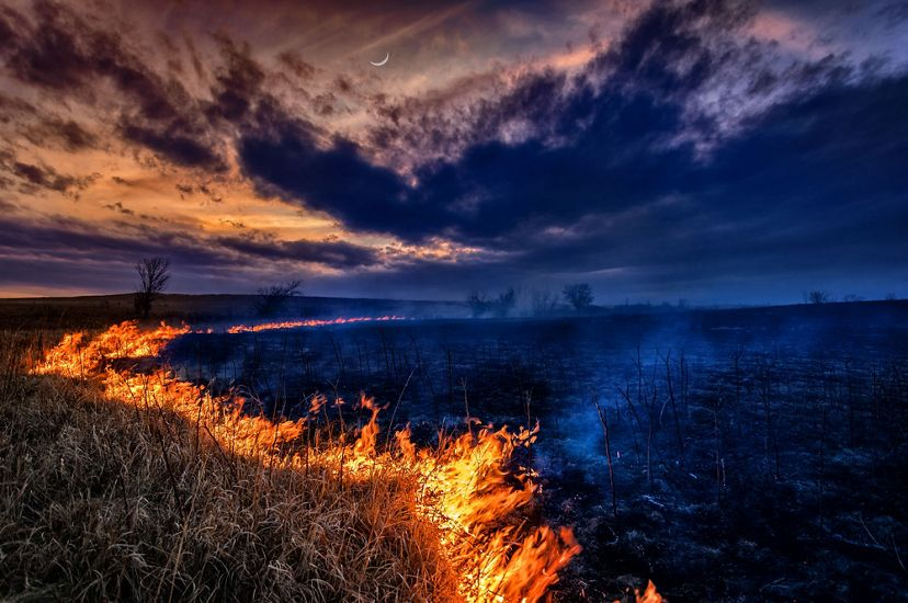 burning line of grass on a prairie with smoke and a crescent moon