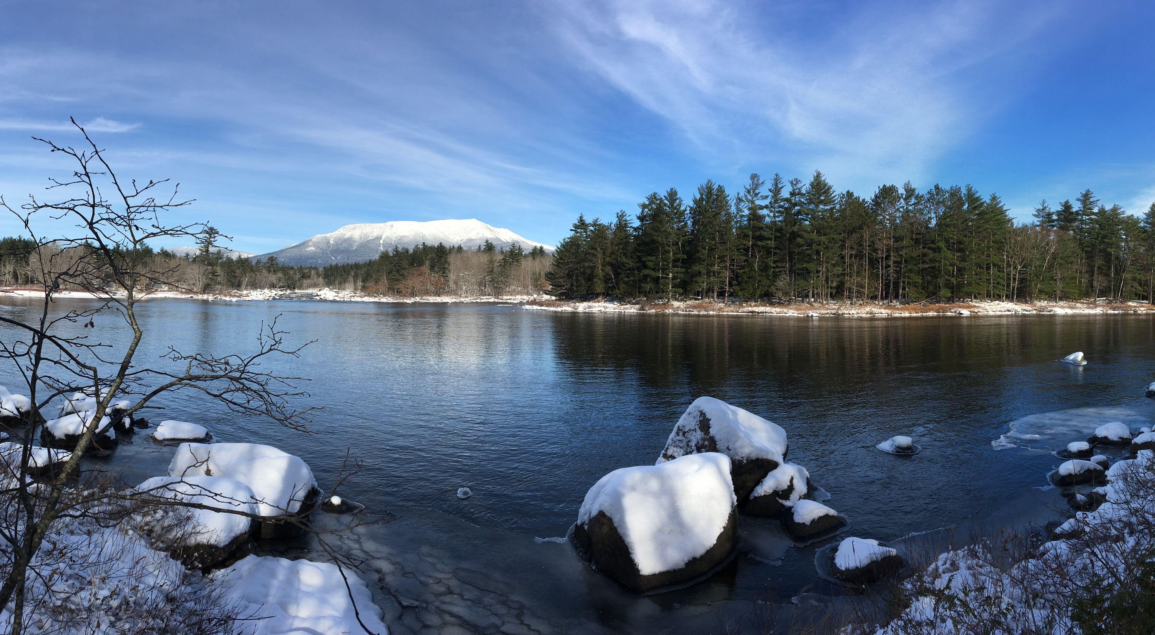 A view across a river of a distant Mount Katahdin with snow on its slopes.
