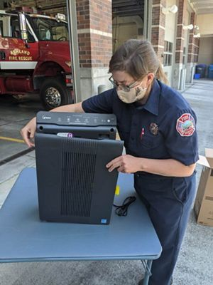 A woman firefighter in station clothes inspects an air purifier outside the Ashland, Oregon, fire station.