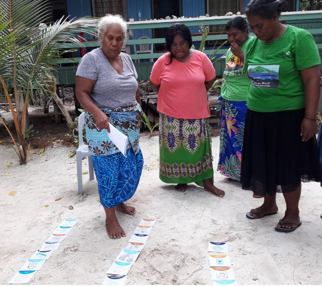 A few women look at cards in the sand during a KAWAKI women's leadership training in 2019.