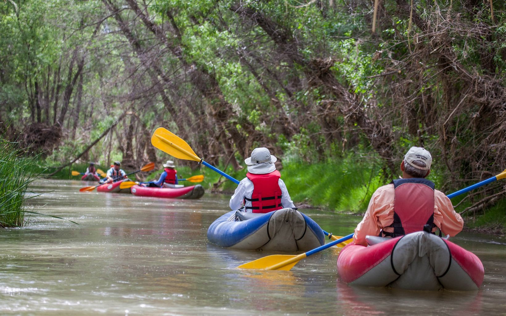 Four kayakers paddle away down the muddy waters of the Verde River.