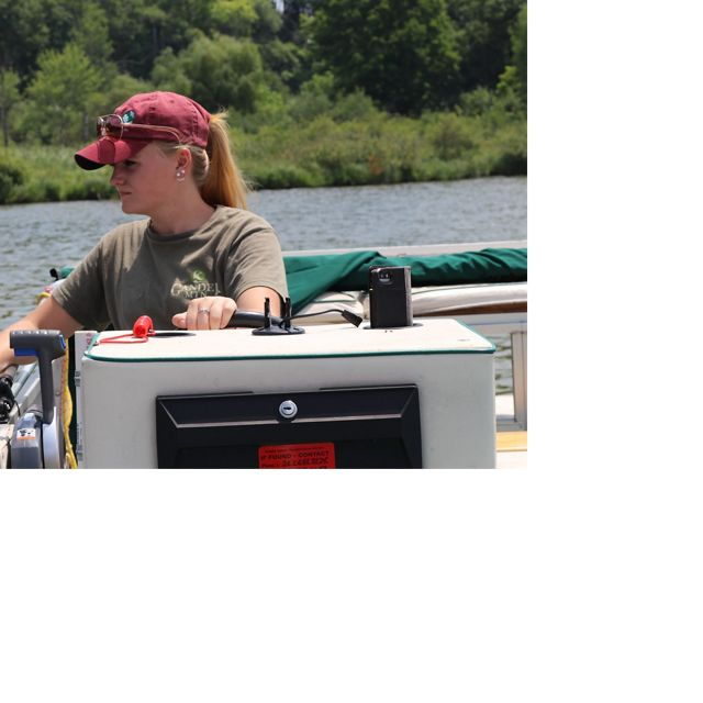 Our intern Kayla drives a pontoon on a lake in the summer.