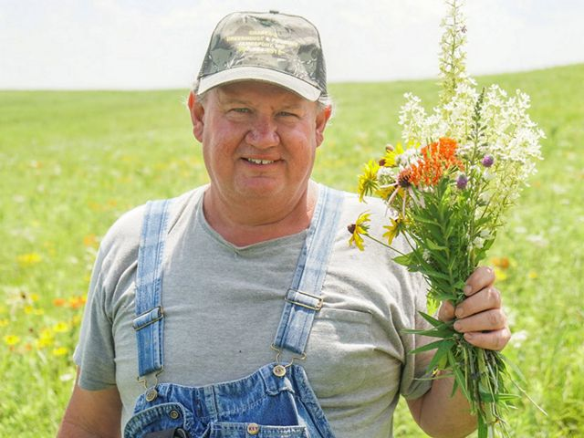 A man stands in front of a blooming prairie holding a bouquet of colorful prairie flowers.