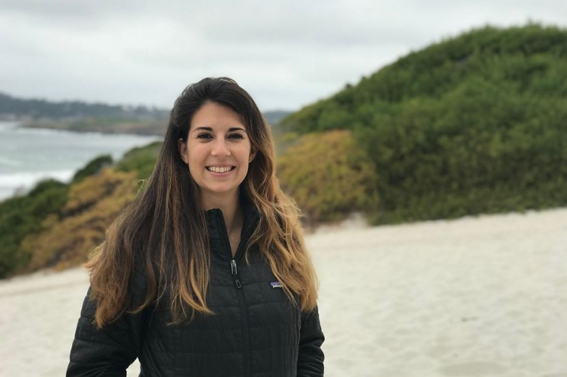 A smiling woman with long brown hair stands on a beach. A grassy dune and crashing waves are visible behind her.